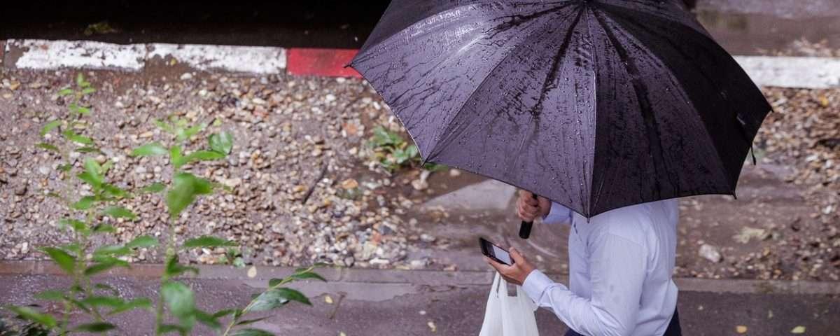 Man walking under an umbrella