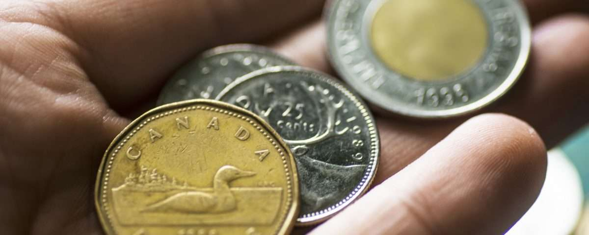 Male hand holding Canadian coins