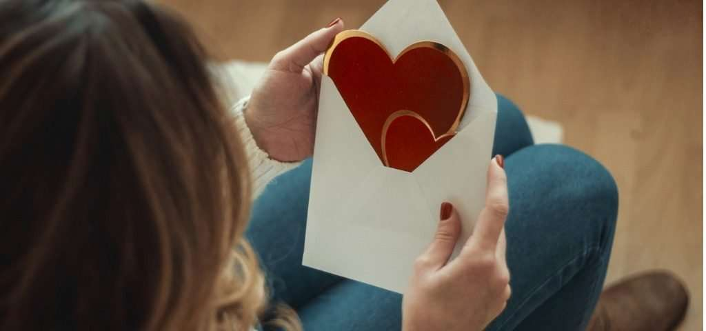 Woman opening a envelope containing a Valentine's card