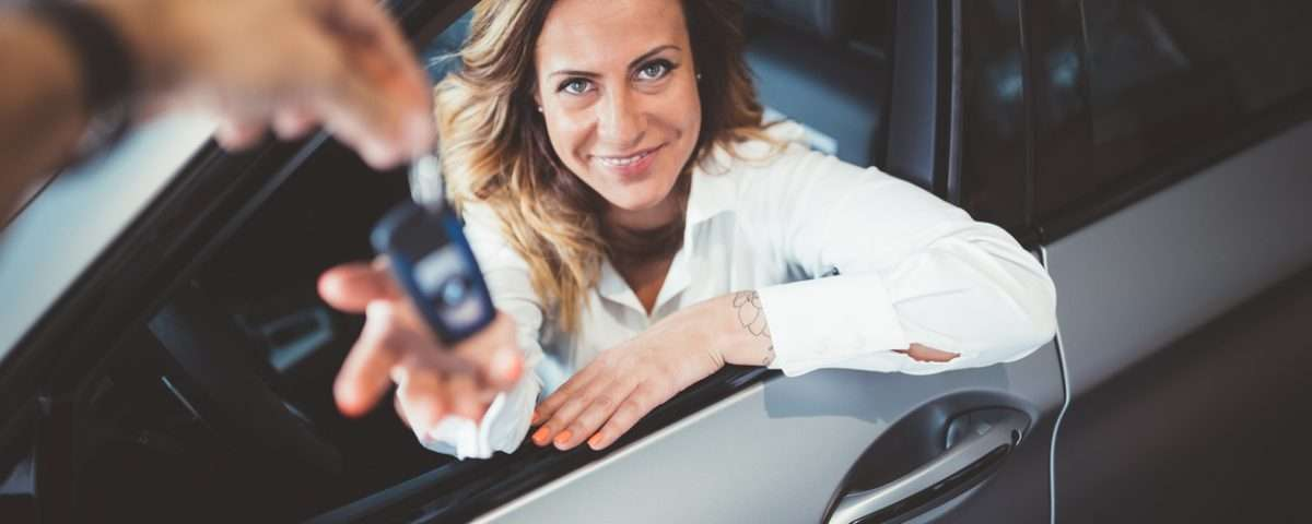 Woman being handed keys to new car