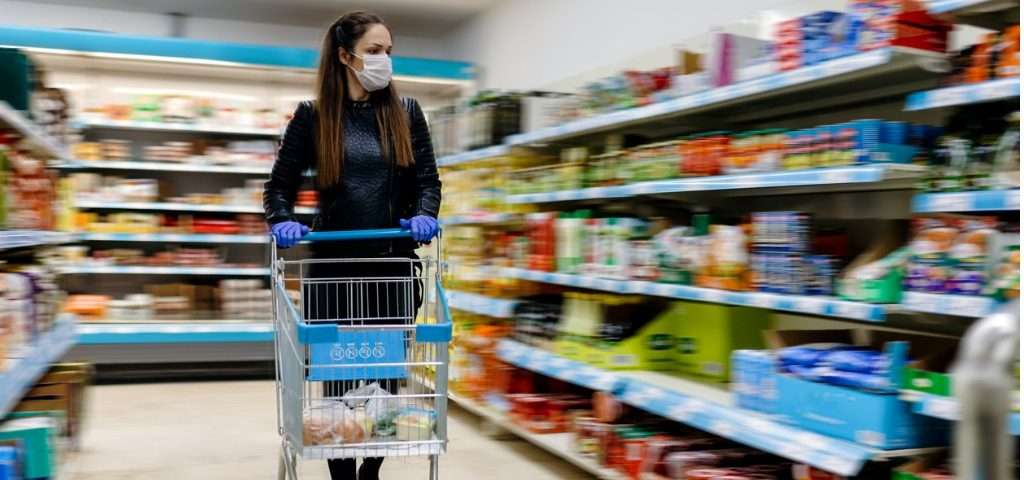 Woman grocery shopping wearing a mask