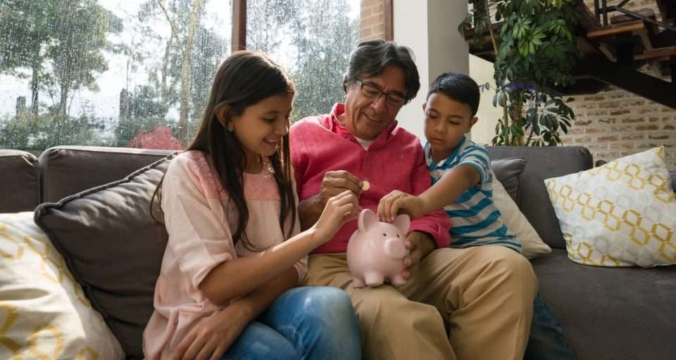 Family putting money in a piggy bank